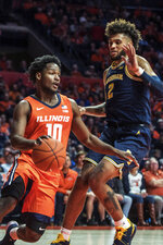 Illinois' Andres Feliz (10) powers past Michigan's Isaiah Livers (2) in the first half of an NCAA college basketball game, Wednesday, Dec. 11, 2019, in Champaign, Ill. (AP Photo/Holly Hart)