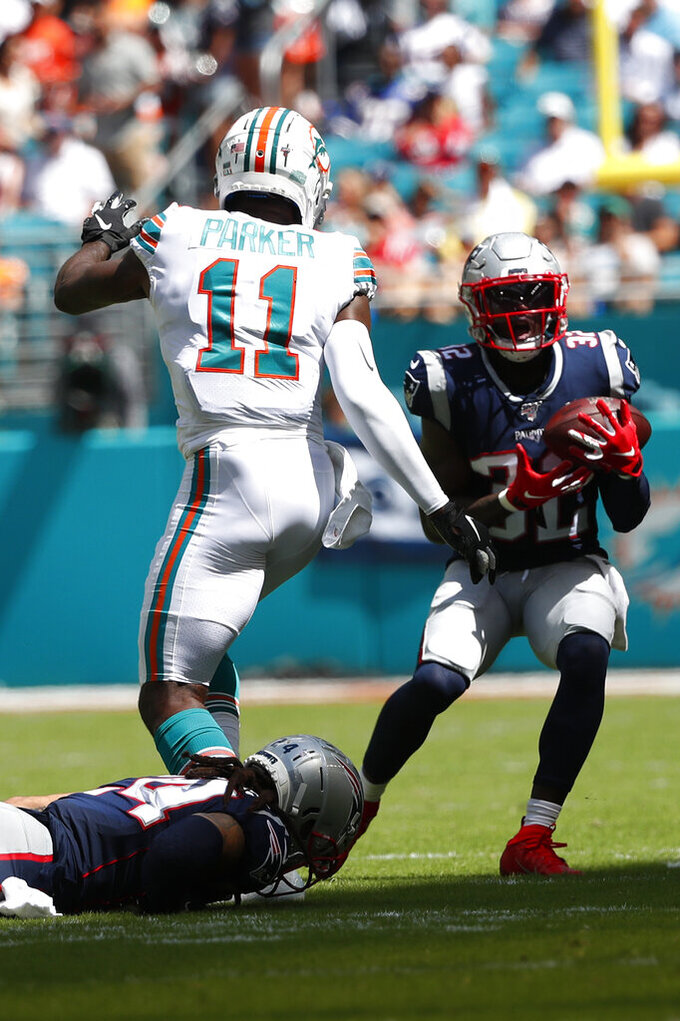 New England Patriots free safety Devin McCourty (32) intercepts a pass intended for Miami Dolphins wide receiver DeVante Parker (11), during the second half at an NFL football game, Sunday, Sept. 15, 2019, in Miami Gardens, Fla. (AP Photo/Wilfredo Lee)