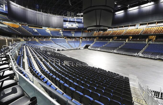 FILE - This is a March 12, 2020, file photo showing empty seats at the Amway Center in Orlando, home of the NBA's Orlando Magic. Most teams and leagues are reticent to discuss the fallout, but during a conference call with players, NBA commissioner Adam Silver told players that 40 percent of the league's revenue comes from ticket sales and in-arena purchases. The NBA makes about $1.2 million in gate revenue for each regular-season game played with fans, and there were 259 games remaining when the season was suspended. (Stephen M. Dowell/Orlando Sentinel via AP, File)
