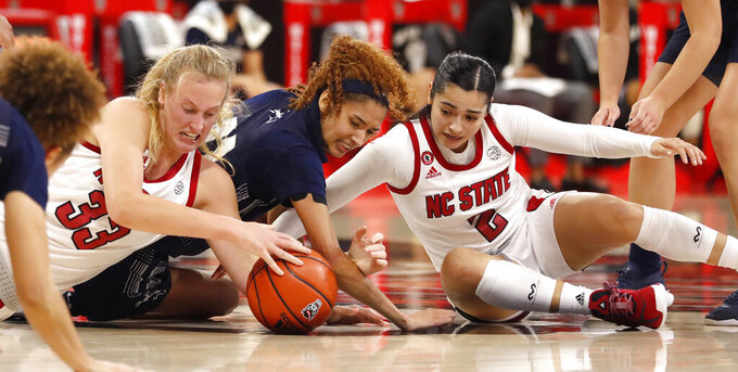 From left, NC State's Elissa Cunane (33), North Florida's Jazz Bond (11) and NC State's Raina Perez (2) go after the loose ball during the first half of an NCAA college basketball game at Reynolds Coliseum in Raleigh, N.C., Wednesday, Nov. 25, 2020. (Ethan Hyman/The News & Observer via AP)