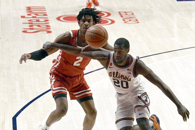 Illinois guard Da'Monte Williams (20) battles for ball control with Wisconsin's forward Aleem Ford (2) in the first half of an NCAA college basketball game Saturday, Feb. 6, 2021, in Champaign, Ill. (AP Photo/Holly Hart)