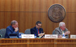 FILE - New Mexico Senate Finance Committee Chairman John Arthur Smith, left, and Sens. Steven Neville, R-Aztec, and Carlos Cisneros, D-Questa, center, broker a compromise between dueling House and Senate budget plans at a conference committee meeting on Wednesday, Feb. 14, 2018, in Santa Fe, New Mexico. Legislative officials confirmed that Cisneros died Tuesday, Sept. 17, 2019 of a heart attack. He had served in the Senate since 1985. (AP Photo/Morgan Lee)