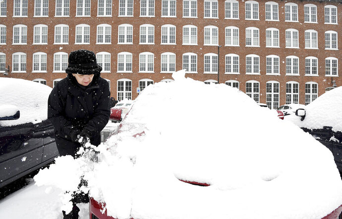 Sue Baker clears snow from her car at the Sterling Lofts apartments Tuesday, Dec. 3, 2019 in Attleboro, Mass. The area received several new inches of snow overnight. (Mark Stockwell/The Sun Chronicle via AP)