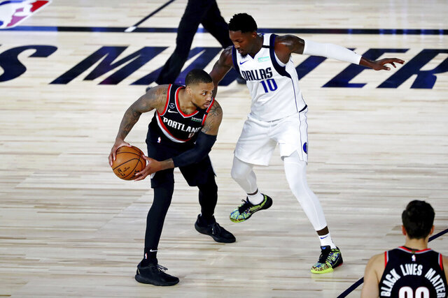Portland Trail Blazers guard Damian Lillard holds the ball while defended by Dallas Mavericks forward Dorian Finney-Smith (10) during the second half of an NBA basketball game Tuesday, Aug. 11, 2020, in Lake Buena Vista, Fla. (Kim Klement/Pool Photo via AP)