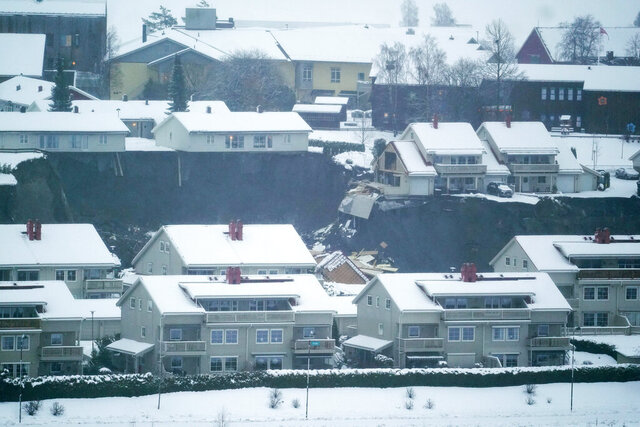 Some houses remain standing while others are seen damaged after a landslide occurred in a residential area in Ask, near Oslo, Wednesday, Dec. 30, 2020. Several houses have been destroyed, up to 200 people have been evacuated and nine injured in Norway in a landslide at a residential area near the capital Oslo. Norwegian police were alarmed around 4 am Wednesday that a landslide had occured in the village of Ask in the municipality of Gjerdrum, some thirty kilometers (12 miles) north of Oslo. (Fredrik Hagen/NTB via AP)