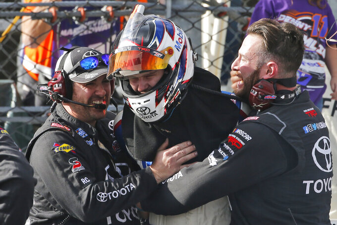 Todd Gilliland, center, gets a hug from his pit crew as he celebrates winning the NASCAR Truck Series race at Martinsville Speedway in Martinsville, Va., Saturday, Oct. 26, 2019, (AP Photo/Steve Helber)