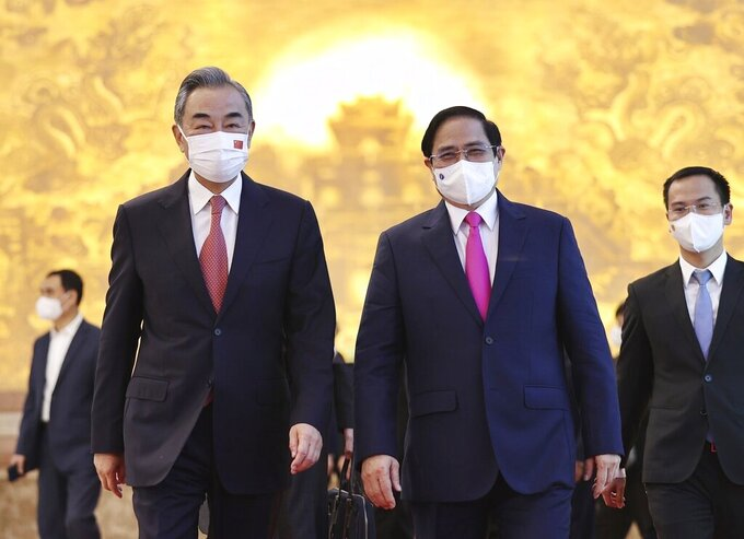 Vietnamese Prime Minister Pham Minh Chinh and Chinese Foreign Minister Wang Yi walk into meeting room in Hanoi, Vietnam on Saturday, Sep.11, 2021. China has pledged to donate 3 million doses of its vaccine to Vietnam as Foreign Minsiter Wang Yi closed his visit to Hanoi. (Duong Van Giang/VNA via AP)