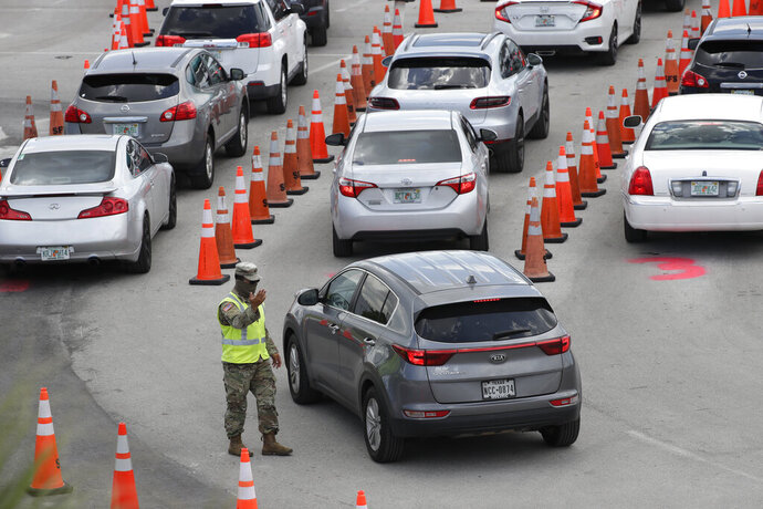 A National Guardsman directs traffic at a COVID-19 testing site outside Hard Rock Stadium, Wednesday, July 8, 2020, in Miami Gardens, Fla. Florida is one of the nation's hot spots for coronavirus. (AP Photo/Wilfredo Lee)