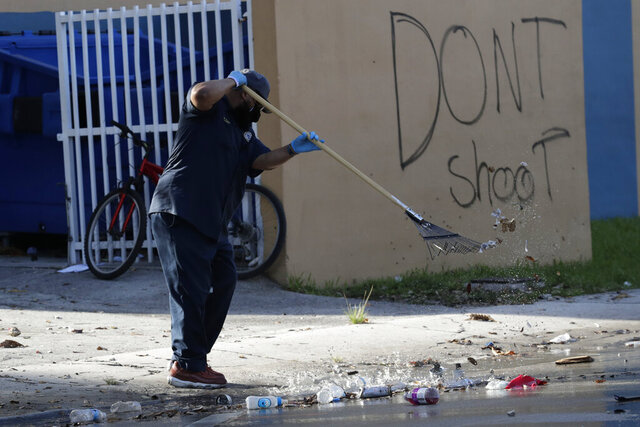 A City of Miami employee cleans up debris from the street next to graffiti reading