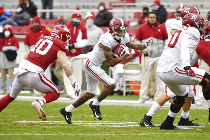 Alabama receiver DeVonta Smith (6) runs for a gain against Arkansas during an NCAA college football game Saturday, Dec. 12, 2020, in Fayetteville, Ark. (AP Photo/Michael Woods)