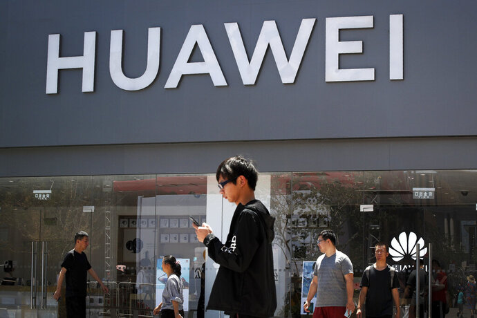 People walk past a Huawei retail store in Beijing, Sunday, June 30, 2019. Once again, Presidents Donald Trump and Xi Jinping have hit the reset button in trade talks between the world's two biggest economies, at least delaying an escalation in tension between the U.S. and China that had financial markets on edge and cast a cloud over the global economy. (AP Photo/Andy Wong)