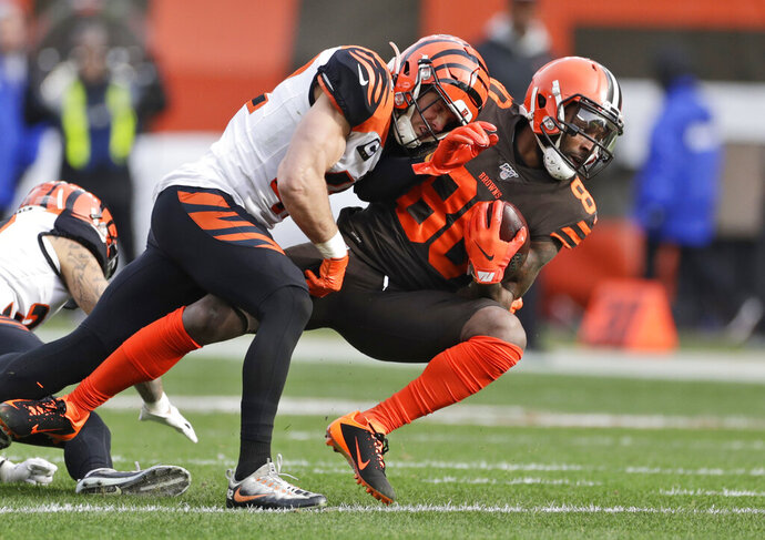 Cincinnati Bengals defensive back Clayton Fejedelem (42) tackles Cleveland Browns wide receiver Jarvis Landry (80) during the first half of an NFL football game, Sunday, Dec. 8, 2019, in Cleveland. (AP Photo/Ron Schwane)