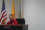"""Otero County Commissioner Couy Griffin presides at a public meeting in Alamogordo, N.M., on Thursday, May 13, 2021, in a shirt with a """"C4T"""" logo that stands for Cowboys for Trump. Griffin founded the support group for President Trump that held horseback parades across the country. Griffin is reviled and revered in politically conservative Otero County as he confronts criminal charges for joining protests on the steps of the U.S. Capitol on Jan. 6. He is fighting for his political future amid a recall initiative and state probes into his finances. (AP Photo/Morgan Lee)"""