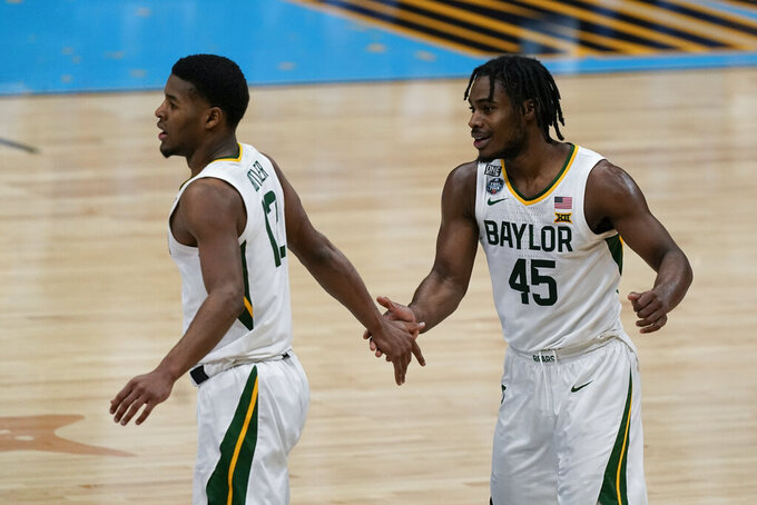Baylor guard Davion Mitchell (45) celebrates with teammate guard Jared Butler (12) during the first half of a men's Final Four NCAA college basketball tournament semifinal game against Houston, Saturday, April 3, 2021, at Lucas Oil Stadium in Indianapolis. (AP Photo/Michael Conroy)
