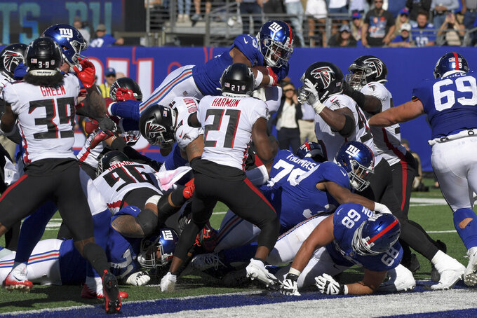 New York Giants running back Saquon Barkley (26) dives over a scrum on a touchdown run during the second half of an NFL football game against the Atlanta Falcons, Sunday, Sept. 26, 2021, in East Rutherford, N.J. (AP Photo/Bill Kostroun)