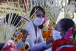 Women wearing face masks wait to join a parade in Bali, Indonesia, on Thursday, July 30, 2020. Indonesia's resort island of Bali will reopen for domestic tourists on Friday after months of virus lockdown. (AP Photo/Firdia Lisnawati)