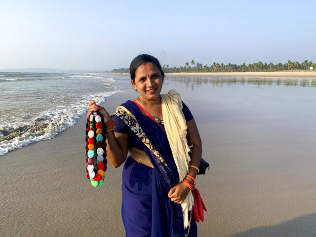 Seema Rajgarh, 37, hawks jewelry made of beads and stones on nearly deserted Utorda beach in South Goa, India,, Dec.16, 2020. On good days during the holiday season, the mother of three girls, the youngest not yet two years old, said she used to make 2,000 rupees ( $27). Now, times are bleak.