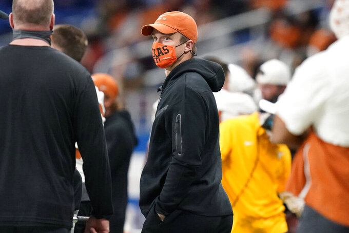 Texas quarterback Sam Ehlinger, center, stands on the sideline after he left the game with a shoulder injury during the second half of the team's Alamo Bowl NCAA college football game against Colorado, Tuesday, Dec. 29, 2020, in San Antonio. (AP Photo/Eric Gay)