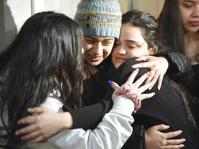 Meydi Guzman, right, a Crystal Lake Central High School senior who was in U.S. Immigration and Customs custody for several months, embraces friends as she is welcomed back at the home of school counselor Sara Huser on Thursday, Feb. 13, 2020, in Crystal Lake, Ill. Guzaman's supporters plan to continue a fight against her deportation to Honduras. (John Starks/Daily Herald via AP)