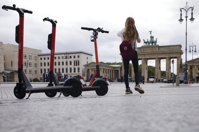 Electric scooters stand in front of the Brandenburg Gate and wait for customers in Berlin, Germany, Tuesday, Sept. 17, 2019. Berlin police say in the three months since popular electric scooters have been allowed in the German capital, they've seen 74 accidents, 65 cases of drunken driving and 233 traffic violations. (AP Photo/Markus Schreiber)