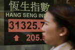 A woman walks past an electronic stock board showing the Hang Seng Index at a bank in Hong Kong, Friday, Jan. 12, 2018. Most Asian stocks markets were mixed Friday, as Wall Street's latest record close and strong oil prices were offset by the strengthening yen, which pressured Japan's Nikkei.(AP Photo/Kin Cheung)