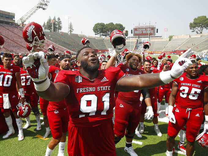 Fresno State defensive tackle Matt Lawson celebrates with the band after Fresno State defeated Connecticut in an NCAA college football game in Fresno, Calif., Saturday, Aug. 28, 2021. (AP Photo/Gary Kazanjian)