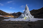 In this image released by World Press Photo, Thursday April 15, 2021, by Ciril Jazbec for National Geographic, titled One Way to Fight Climate Change: Make Your Own Glaciers, which won the second prize in the Environment Stories category, shows the youth group that built this ice stupa in the village of Gya installed a café in its base in India, March 19, 2019. They used the proceeds to take the village elders on a pilgrimage. (Ciril Jazbec for National Geographic, World Press Photo via AP)