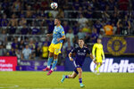 Philadelphia Union defender Kai Wagner (27) heads the ball on a pass next to Orlando City forward Chris Mueller during the second half of an MLS soccer match Thursday, July 22, 2021, in Orlando, Fla. (AP Photo/John Raoux)