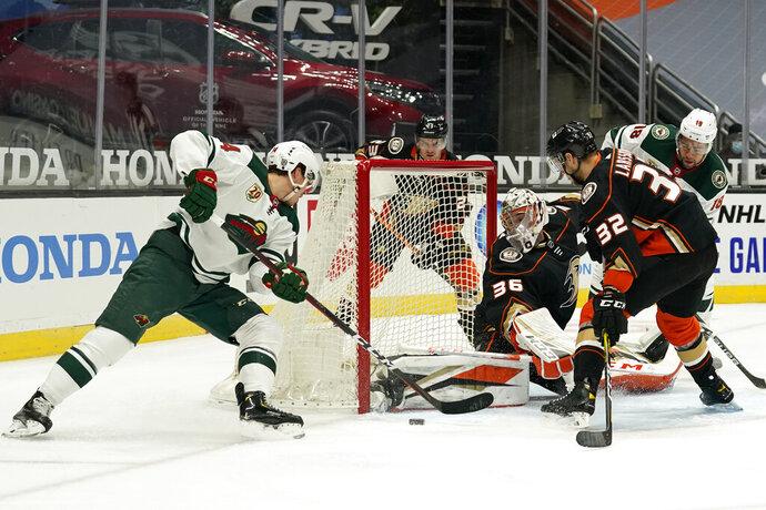 Anaheim Ducks goaltender John Gibson, center, stops a shot from Minnesota Wild center Joel Eriksson Ek during the first period of an NHL hockey game Monday, Jan. 18, 2021, in Anaheim, Calif. (AP Photo/Marcio Jose Sanchez)