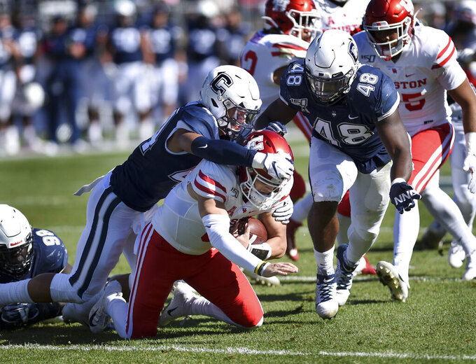 Houston quarterback Logan Holgorsen is sacked by Connecticut linebacker Ian Swenson (44) during the first half of an NCAA college football game, Saturday, Oct. 19, 2019, in East Hartford, Conn. (AP Photo/Stephen Dunn)