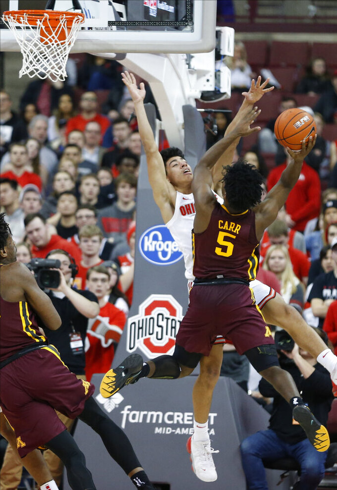Minnesota's Marcus Carr, right, shoots over Ohio State's D.J. Carton during the second half of an NCAA college basketball game Thursday, Jan. 23, 2020, in Columbus, Ohio.  (AP Photo/Jay LaPrete)