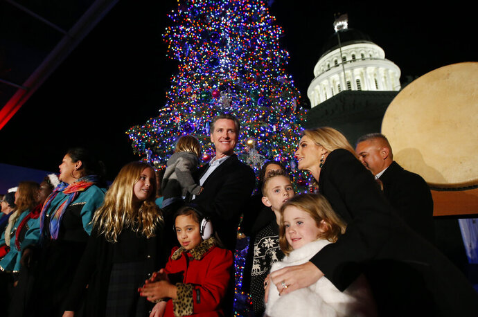 Gov. Gavin Newsom, center, holding his son, Dutch is joined by his wife first partner Jennifer Siebel Newsom right, and family after the lighting of the Capitol Christmas Tree, Sacramento, Calif., Thursday, Dec. 5, 2019. The more than 65-foot-tall white fir tree is decorated with hundreds of hand-crafted ornaments donated from the California Department of Developmental Services and 10,000 ultra-low-wattage LED lights. .(AP Photo/Rich Pedroncelli)