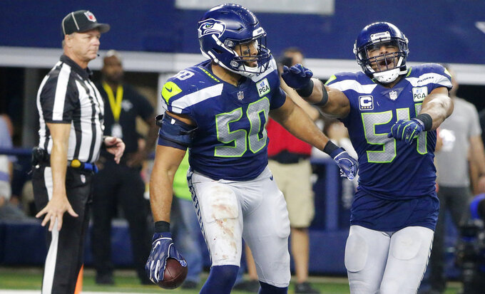 Seattle Seahawks' K.J. Wright (50) and Bobby Wagner (54) celebrate an interception against Dallas Cowboys quarterback Dak Prescott during the second half of the NFC wild-card NFL football game in Arlington, Texas, Saturday, Jan. 5, 2019. (AP Photo/Michael Ainsworth)