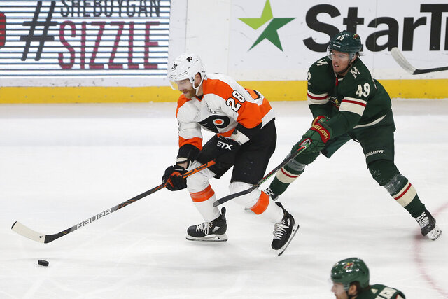 Philadelphia Flyers' Claude Giroux and Minnesota Wild's Victor Rask skate after the puck in the first period of an NHL hockey game Saturday Dec. 14, 2019, in St. Paul, Minn. (AP Photo/Stacy Bengs)