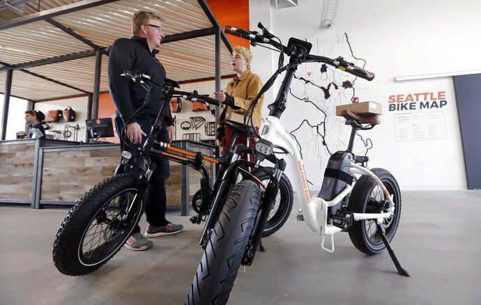 In this photo taken Wednesday, May 15, 2019, customer Torre Treece, left, talks with Rad Power Bikes sales associate Becs Richards about the two electric bikes he bought at the shop in Seattle. The bicycle company said that they will absorb 100% of any tariff on their Chinese-made bicycles. (AP Photo/Elaine Thompson)