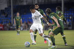 LA Galaxy forward Cristian Pavon (10) controls the ball in front of Portland Timbers defender Jorge Villafana, front, midfielder Diego Chara (21) and midfielder Eryk Williamson during the second half of an MLS soccer match Monday, July 13, 2020, in Kissimmee, Fla. (AP Photo/Phelan M. Ebenhack)