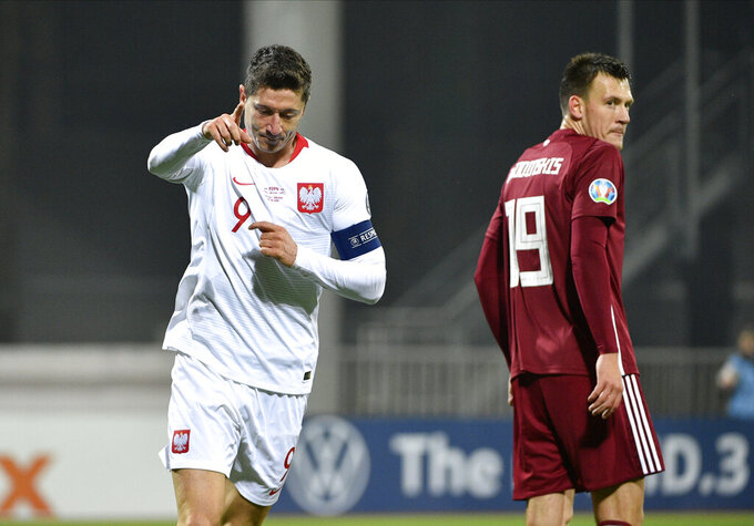 FILE - In this Thursday, Oct. 10, 2019 file photo, Poland's Robert Lewandowski reacts as he scores his second goal during Euro 2020 group G qualifying soccer match in Riga, Latvia. With a chance to become the all-time top scorer with a national team, Cristiano Ronaldo will highlight the list of top players at this year's European Championship. Others who could make an impact include Kylian Mbappé, Robert Lewandowski, Kevin De Bruyne and Harry Kane. (AP Photo/Roman Koksarov, File)