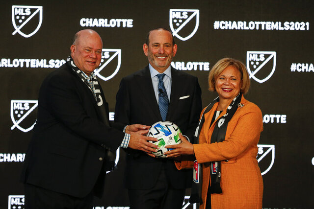 Major League Soccer Commissioner Don Garber, left, Charlotte MLS owner David Tepper, center, and Charlotte mayor Vi Lyles pose for a photo after announcing the MLS will have a team in Charlotte in 2021 at an event in Charlotte, N.C., Tuesday, Dec. 17, 2019. (AP Photo/Nell Redmond)