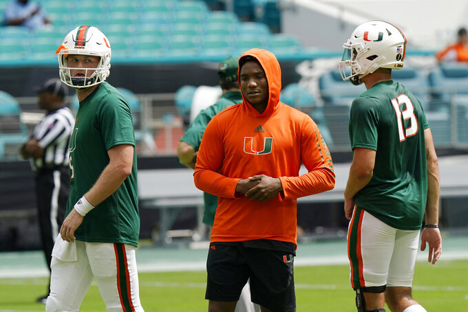 Miami starting quarterback D'Eriq King, center, stands with quarterbacks Tyler Van Dyke (9) and Jake Garcia (13) before an NCAA college football game against Central Connecticut State, Saturday, Sept. 25, 2021, in Miami Gardens, Fla. King is not playing due to an injury. (AP Photo/Lynne Sladky)