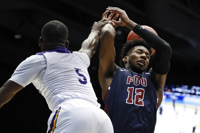 Prairie View A&M's Kevonte Corley (5) blocks a shot by Fairleigh Dickinson's Kaleb Bishop (12) during the second half of a First Four game of the NCAA college basketball tournament, Tuesday, March 19, 2019, in Dayton, Ohio. (AP Photo/John Minchillo)