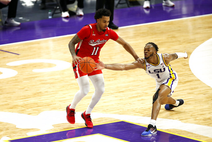 LSU guard Ja'Vonte Smart (1) reaches for the ball from Texas Tech guard Kyler Edwards (11) in the second half of an NCAA college basketball game in Baton Rouge, La., Saturday, Jan. 30, 2021. Texas Tech won 76-71. (AP Photo/Tyler Kaufman)
