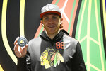 Chicago Blackhawks right wing Patrick Kane (88) poses with the puck after getting his 1,0000th point on an assist against the Winnipeg Jets after an NHL hockey game Sunday, Jan. 19, 2020, in Chicago. (AP Photo/David Banks)