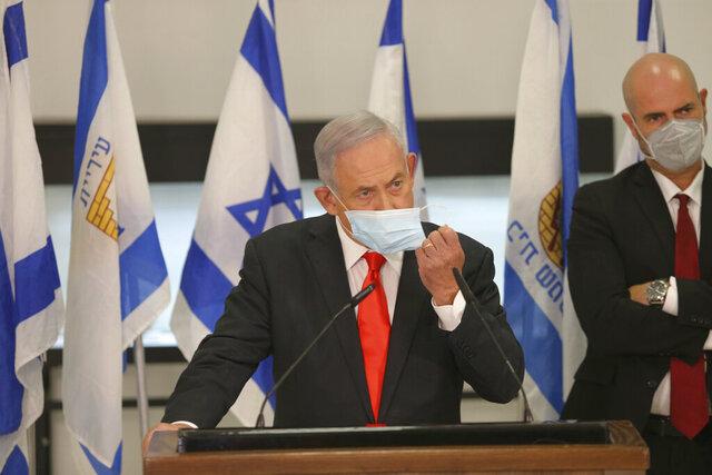 Israeli Prime Minister Benjamin Netanyahu adjusts his face mask during his visit to the Israeli city of Beit Shemesh, near Jerusalem, Tuesday, Sept. 8, 2020. (Alex Kolomoisky/Pool Photo via AP)