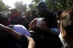 FILE - In this Oct. 24, 2019 file photo, protesters carry away an injured colleague during clashes with police in Santiago, Chile.In less than a month, more than 230 Chileans have lost sight in one eye, mostly due to the impact of pellets fired by the police during clashes with protesters demanding greater equality and improved social services. (AP Photo/Rodrigo Abd, File)