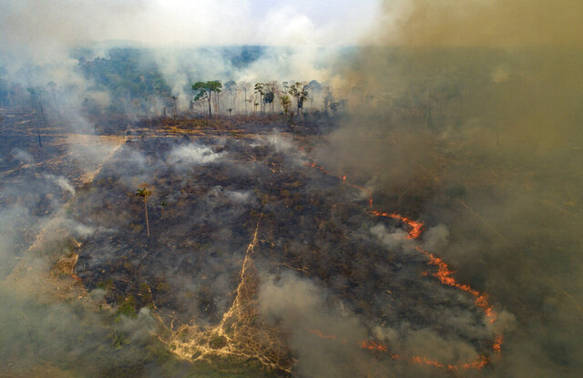 Fire consumes land deforested by cattle farmers near Novo Progresso, Para state, Brazil, Sunday, Aug. 23, 2020. Under military command, Brazil's once-effective investigation and prosecution of illegal rainforest destruction by ranchers, farmers and miners has come to a virtual halt, even as this year's burning season is about to begin. (AP Photo/Andre Penner)