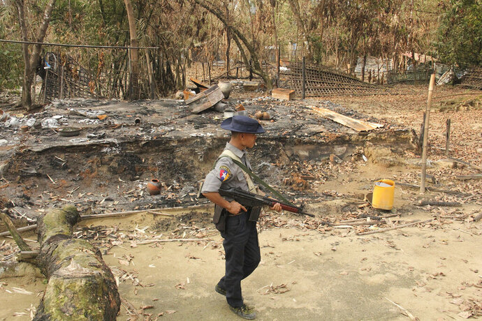 FILE - In this Sept. 6, 2017, file photo, a Myanmar security officer walks past burned Rohingya houses in Ka Nyin Tan village of suburb Maungdaw, northern Rakhine state of western Myanmar. Myanmar's government announced Wednesday, Nov. 20, 2019 that its leader, Aung San Suu Kyi, will head a legal team it will send to the International Court of Justice in the Netherlands to contest a case of genocide filed against it by Gambia on behalf of the Organization of Islamic Cooperation. (AP Photo, File)