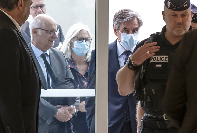 France's former Prime Minister Francois Fillon, right, and his wife Penelope wear protective masks as they arrive at Paris courthouse, in Paris, Monday, June 29, 2020. A Paris court is set to render or postpone a verdict in the fraud trial of former Prime Minister Francois Fillon on Monday. (AP Photo/Michel Euler)