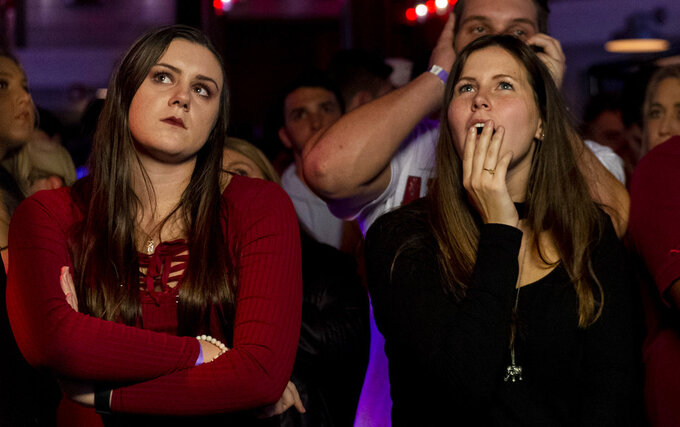 Megan Richardson, left, and Miciah Hirr react as Alabama falls behind as they watch a broadcast of an NCAA college football playoff championship game against Clemson, Monday, Jan. 7, 2019, at Rounders on the Strip in Tuscaloosa, Ala. (AP Photo/Vasha Hunt)