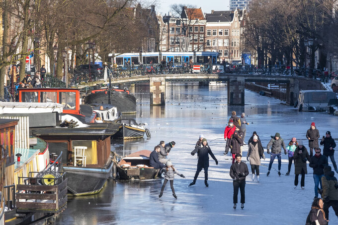 Dozens of skaters took to the frozen surface of Amsterdam's historic Prinsengracht canal in Amsterdam, Netherlands, Saturday, Feb. 13, 2021, as the deep freeze gripping Europe briefly made it possible to skate on a small section of the canal for the first time since 2018. People skated and walked on a small stretch of ice between two bridges close to the landmark Westerkerk before growing cracks in the ice forced all but the most daring off the ice. in Amsterdam, Netherlands, Saturday, Feb. 13, 2021. (AP Photo/Patrick Post)