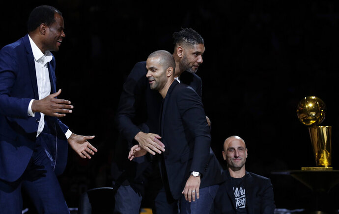 Former San Antonio Spurs guard Tony Parker, front center, is congratulated by former teammates, from left, David Robinson, Tim Duncan and Manu Ginobili, seated, during Parker's retirement ceremony after the team's NBA basketball game against the Memphis Grizzlies in San Antonio, Monday, Nov. 11, 2019. (AP Photo/Eric Gay)